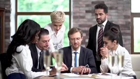 Friendly colleagues at a business meeting with a champagne. Concentrated Man At The Head Of The Table Looks At Tablet And Holds A Phone While His Colleagues Show stock video