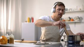 Concentrated man in headphones listening music and cooking tasty meal, leisure