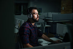 Concentrated man in headphones working at night dark office. Concentrated handsome young man in headphones sitting and working at night in dark office Royalty Free Stock Photos
