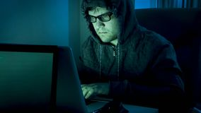 Concentrated young man in hood typing program code on laptop at night. Concentrated man in hood typing program code on laptop at night Royalty Free Stock Photos