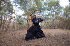 Concentrated man with a Japanese sword, a katana practicing Iaid Royalty Free Stock Photo