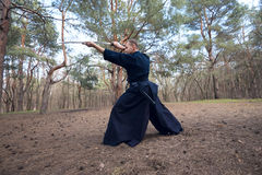 Concentrated man with a Japanese sword, a katana. Wide angle Stock Photo