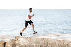 Concentrated man listening to music and running on pier Stock Image