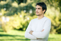 Concentrated man looking away outdoors. Young handsome man outdoors in fall clothing with autumn natural surroundings looking to the side, with copy space Royalty Free Stock Image