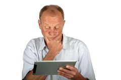 Concentrated man looking at his tablet computerd Stock Photo
