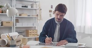 Concentrated man with moustache drawing illustration on tablet . Young guy illustrator using digital notepad and stylus