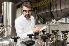 Concentrated man noting work results on beer factory Royalty Free Stock Image