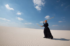 Concentrated man is practicing martial arts in a desert Royalty Free Stock Images
