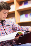Concentrated man reading book in library Stock Photos