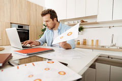 Concentrated man reprinting information from printouts Royalty Free Stock Photography