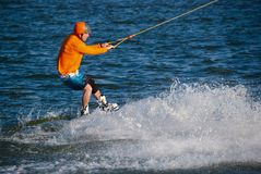 Concentrated man rides fast during training in wakeboarding. Concentrated man, in orange shirt and helmet, rides fast during training in wakeboarding at sunny Stock Photo
