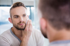 Concentrated man shaving his beard. In bathroom Royalty Free Stock Images