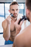Concentrated man shaving his beard. In bathroom Stock Image
