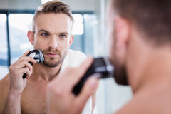 Concentrated man shaving his beard. In bathroom royalty free stock photo
