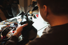 Concentrated man shoemaker at footwear workshop. Picture of young concentrated man shoemaker at footwear workshop Royalty Free Stock Image