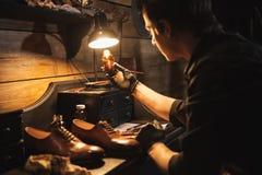 Concentrated man shoemaker at footwear workshop. Picture of young concentrated man shoemaker at footwear workshop Stock Image