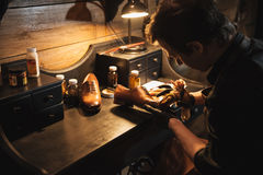 Concentrated man shoemaker at footwear workshop. Picture of young concentrated man shoemaker at footwear workshop Royalty Free Stock Images