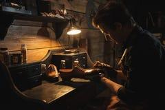 Concentrated man shoemaker at footwear workshop. Picture of young concentrated man shoemaker at footwear workshop stock images