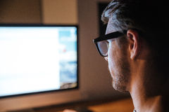 Concentrated man sitting and looking at screen of monitor Stock Photos