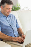 Concentrated man sitting on a sofa typing on a laptop Royalty Free Stock Photography
