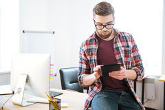Concentrated man sitting on table in office and using tablet Stock Photo