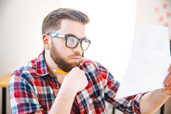 Concentrated man sitting on workplace and examined blueprint Royalty Free Stock Image