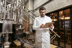 Concentrated man standing at beer factory Royalty Free Stock Photos