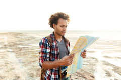 Concentrated man standing outdoors and exploring map. Concentrated african american young man standing outdoors and exploring map Royalty Free Stock Photography