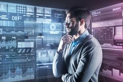 Concentrated man thoughtfully looking at the screen while working Stock Photos