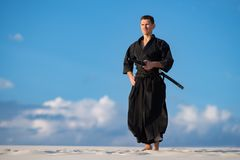 Man meditating before martial arts training. Concentrated man, in traditional Japanese clothes, with sword, katana meditating before the start of martial arts Stock Photos