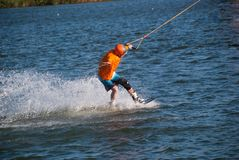 Concentrated man trains on a wakeboard. In the cable park on a sunny day. Active vacation in outdoor Royalty Free Stock Image