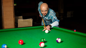 Concentrated man try to hit the cue ball on pool table Stock Image