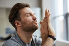 Concentrated man with twisted arms. Concentrated serene handsome young man with stubble keeping eyes closed and twisting arms while meditating royalty free stock photos