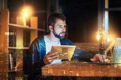 Concentrated man typing a text while holding a tablet in his hands. Two devices. Attentive young bearded man sitting at the table and looking at the screen of a Stock Photos