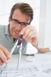 Concentrated man using compass on design Stock Photography