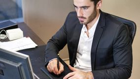 Concentrated man using graphic tablet in office stock footage