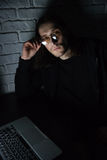 Concentrated man using laptop computer at home. Image of young concentrated man wearing glasses using laptop computer at home indoors at night. Looking at camera Royalty Free Stock Photography