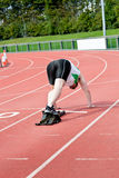 Concentrated man waiting in starting block. In a stadium Royalty Free Stock Photos