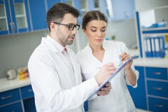 Concentrated man and woman scientists writing in notepad in lab Stock Photos