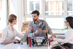 Concentrated man and women sitting at table. Work together. Positive engineer holding robot while communicating with his colleagues in office. Window in the Stock Images