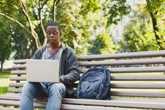 Concentrated man working on his laptop outdoors. Concentrated african-american man working on his laptop, sitting on bench in park. Technology, communication Stock Photos