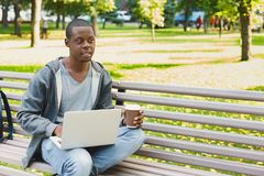 Concentrated man working on his laptop outdoors. Concentrated african-american man working on his laptop, sitting on bench in park with coffee, looking away Royalty Free Stock Photos