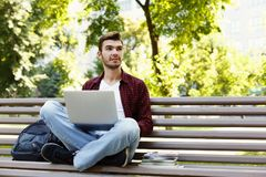 Concentrated man working on his laptop outdoors. Concentrated man working on his laptop, sitting on bench in park, looking away. Technology, communication Stock Images