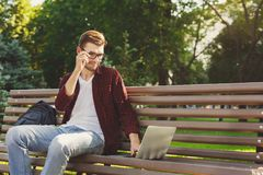 Concentrated man working on his laptop outdoors. Concentrated man in glasses working on his laptop in a pleasant atmosphere outdoors, in the park. Technology Stock Photo