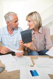 Concentrated mature couple with bills and calculator at home Stock Images