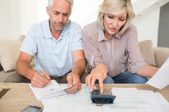 Concentrated mature couple with bills and calculator at home Royalty Free Stock Photos
