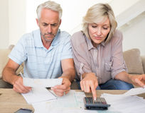 Concentrated mature couple with bills and calculator at home Royalty Free Stock Photo