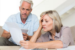 Concentrated mature couple with bills at home Royalty Free Stock Photography