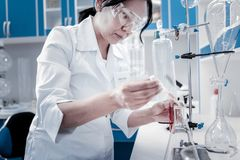 Concentrated mature lady conducting chemical experiment. Controlled experiment. Side view on a focused female scientist using a pipette while working with stock photo