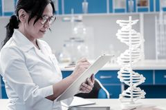 Concentrated mature lady writing something down in laboratory. Genetic studies. Side view on a joyful female medical worker taking some notes while standing next royalty free stock image